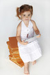 Adorable little girl seated on books is playing with touchpad