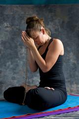woman praying on mat with mala beads