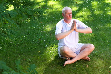 Mature man in yoga prayer pose