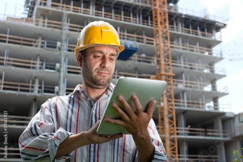 Construction specialist using a tablet.Construction site.