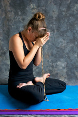 young woman praying on mat with mala beads