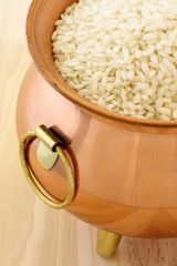 fresh raw risotto on copper pot