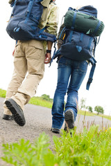 Hiking couple legs backpack on asphalt road