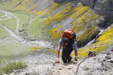 Hombre cruzando un paso complicado en una senda de montaña