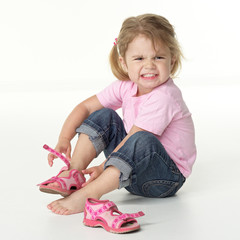 Adorable little girl is annoyed to put on her shoes