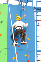 Child climbing on a climbing wall, outdoor