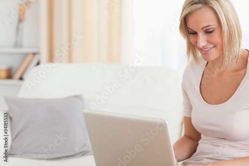 Close up of a smiling woman using a laptop