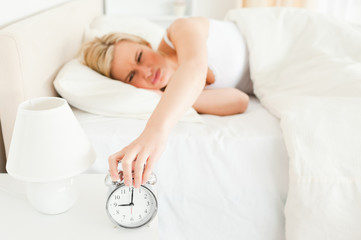 Tired woman switching off her alarm clock