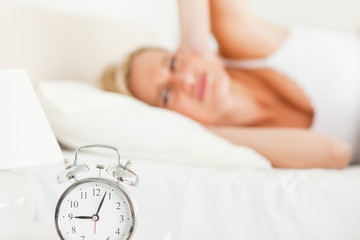 Tired woman awaked by her alarm clock