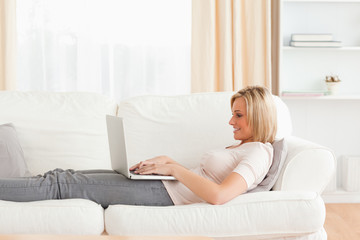 Woman using a laptop while lying on a sofa