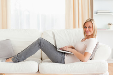 Cute woman with a laptop while lying on a sofa