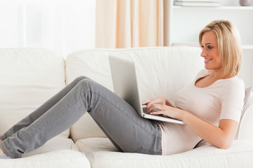 Smiling woman using a laptop while lying on a sofa