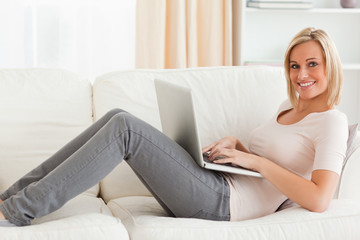 Smiling woman with a laptop while lying on a sofa