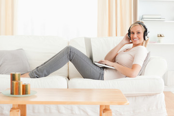 Blond-haired woman with a laptop and headphones