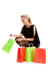 Eine blonde Frau schaut nach dem Einkauf in bunte Papiertüten