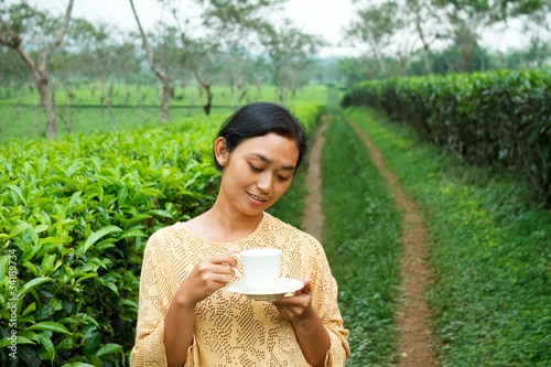 Ethic young woman drinking healthy tea at tea plantation