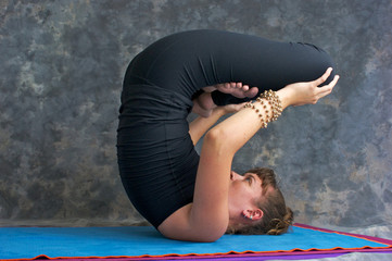 young woman doing yoga asana upward lotus pose