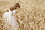 girl wearing first communion dress between barley