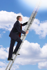 Businessman climbing a ladder in the sky
