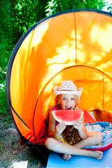 Camping children girl in tent eating watermelon slice
