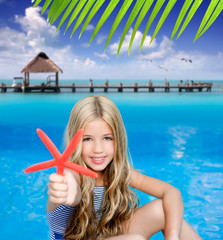 children blond girl in summer  tropical beach with starfish