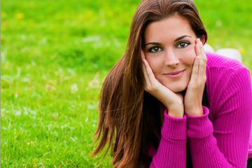 Retrato mujer con manos en la cara y rebeca magenta