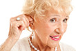Senior Woman Inserts Hearing Aid