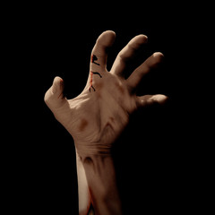 Zombie hand reaching up from a dark place