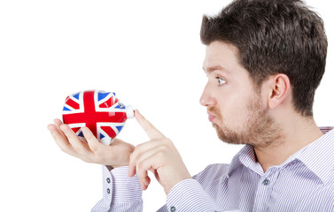 British man playing with piggy bank