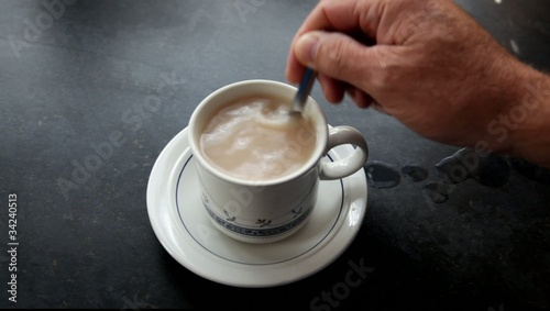 Cup with a teabag being stirred.