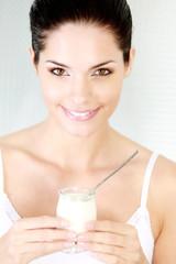 Jeune femme mangeant un yaourt