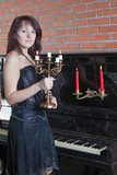 beautiful young woman with candlestick stands near the piano