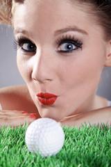 Frau blickt lustig mit Golfball und Kussmund