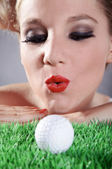 Frau pustet auf Golfball und möchte einlochen