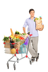 Man with paper bag next to a shopping cart full with groceries