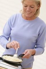 Femme faisant rissoler du riz