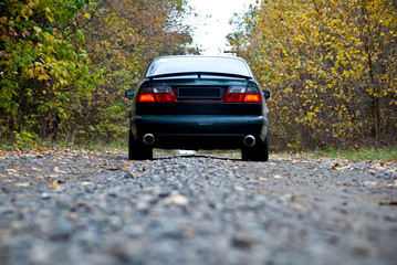 A car on curvy autumn forest road