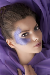 beauty shot of a girl with purple glitter make up laying between