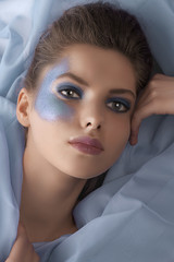 portrait of a model laying between azure sheets