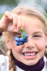 girl holding blueberries in front of her eye smiling