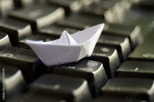 Origami boat on keyboard -Travel and navigating Internet concept