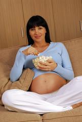 Embarazada comiendo palomitas de maiz.