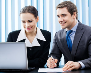 Two happy businesspeople working with laptop at office