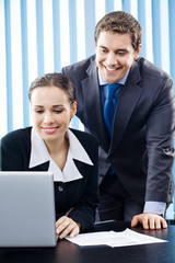 Two happy smiling young businesspeople working with laptop
