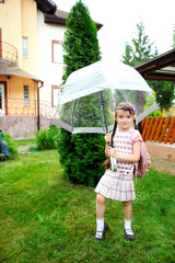 Brunette schoolgirl with backpack under umbrella on a rainy day