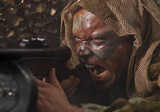 Camouflaged guerrilla soldier screaming and shooting from ambush poster