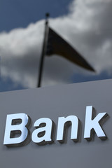 Bank sign on background of sky and flag