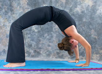 woman doing yoga exercise full wheel pose on on mat in studio