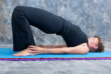 young woman doing yoga exercise on mat in Setu Bandhasanasana or