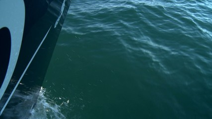 Sailing boat hull close up speeding on sea water